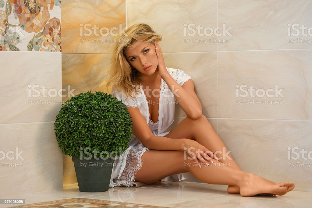 Beautiful woman posing sitting on tiled bathroom floor stock photo