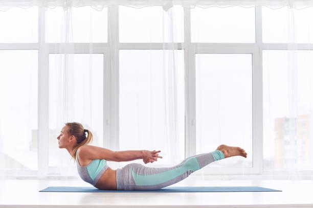 Beautiful woman practices yoga asana Salabhasana - locust pose at the yoga studio Beautiful woman practices yoga asana Salabhasana - locust pose at the bright yoga class with large windows yogi stock pictures, royalty-free photos & images