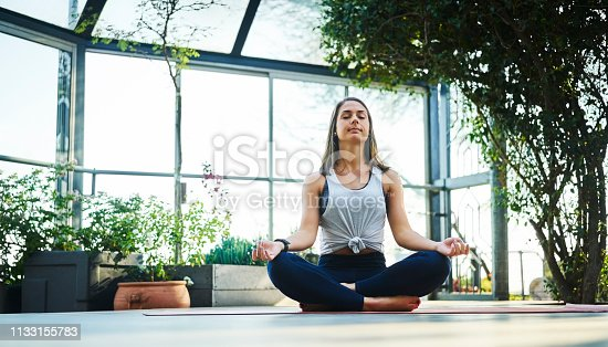 Beautiful young woman practicing lotus position on exercise mat. Full length of fit female is exercising on porch. She is wearing sports clothing.