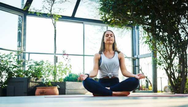 Beautiful woman practicing lotus position on porch stock photo