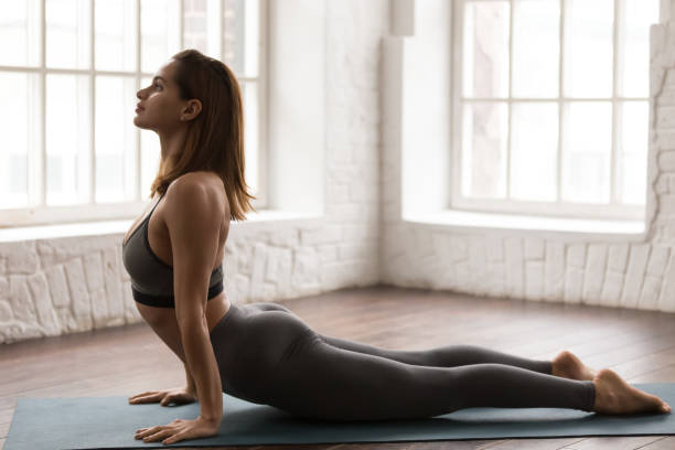 Beautiful woman practicing yoga, lying in Cobra pose, Bhujangasana Young  sporty woman practicing yoga, lying in Cobra pose, doing Bhujangasana exercise, attractive girl in grey sportswear, leggings and bra working out at home or in modern yoga studio cobra pose stock pictures, royalty-free photos & images