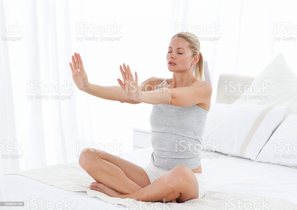 Beautiful woman practicing yoga on her bed royalty-free stock photo