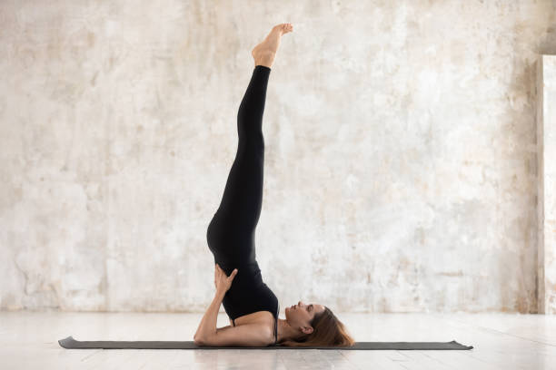 Beautiful woman practicing yoga, Salamba Sarvangasana pose, Shoulder stand Beautiful woman wearing black sportswear practicing yoga, standing in Salamba Sarvangasana pose, doing Shoulder stand exercise, sporty girl working out at home or in yoga studio with grey walls shoulder stand stock pictures, royalty-free photos & images