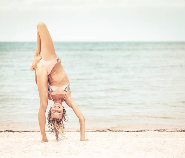 Bella mujer de práctica de Yoga en la costa - foto de stock