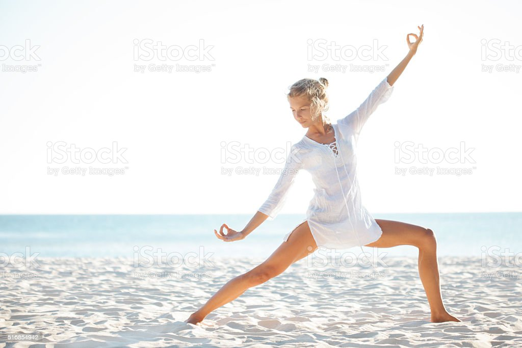 Beautiful woman practising yoga on the shoreline stock photo