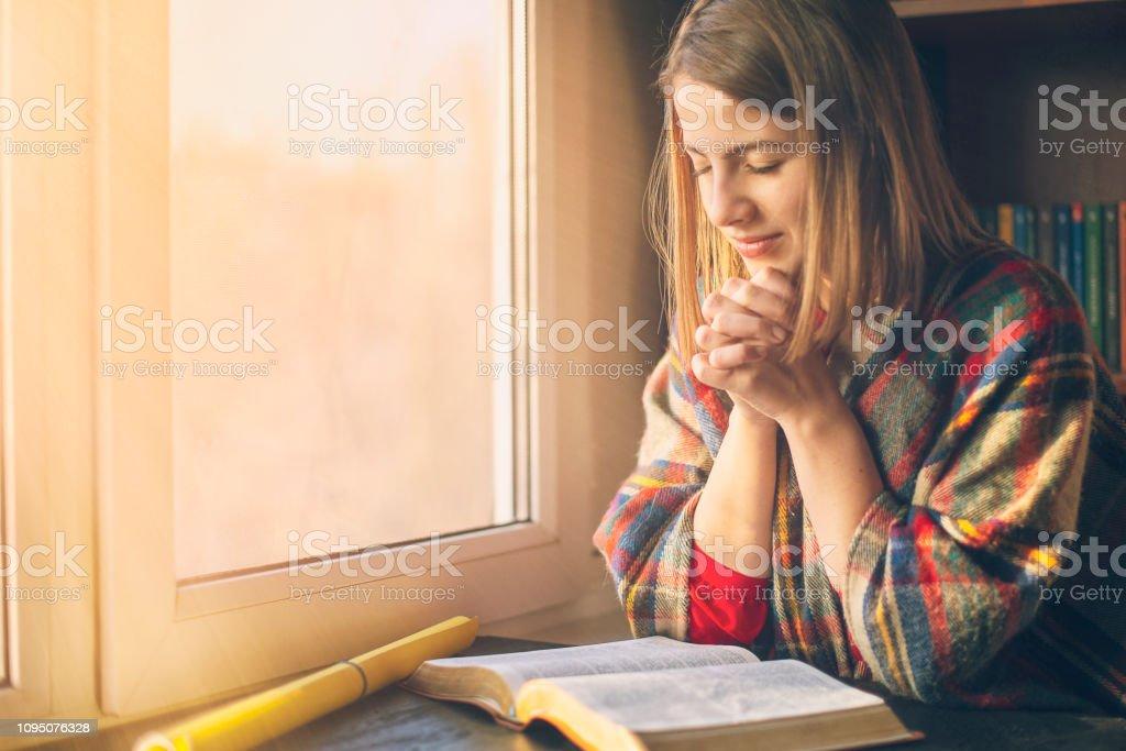 Beautiful woman praying having the Bible opened in front of he - Zbiór zdjęć royalty-free (Biblia)