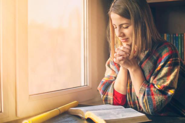 piękna kobieta modląc się o biblię otwartą przed nim - bóg zdjęcia i obrazy z banku zdjęć