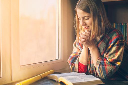 Beautiful Woman Praying Having The Bible Opened In Front Of He - zdjęcia stockowe i więcej obrazów Biblia
