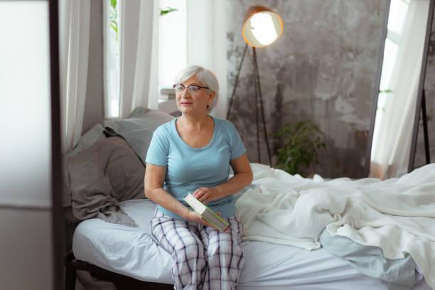 schöne frau, die sich darauf vorbereitet, buch zu öffnen, während sie auf dem bett sitzt. - sexy granny stock-fotos und bilder
