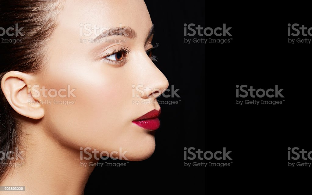 Perfect skin bronze skin caucasian woman isolated on black. Red...