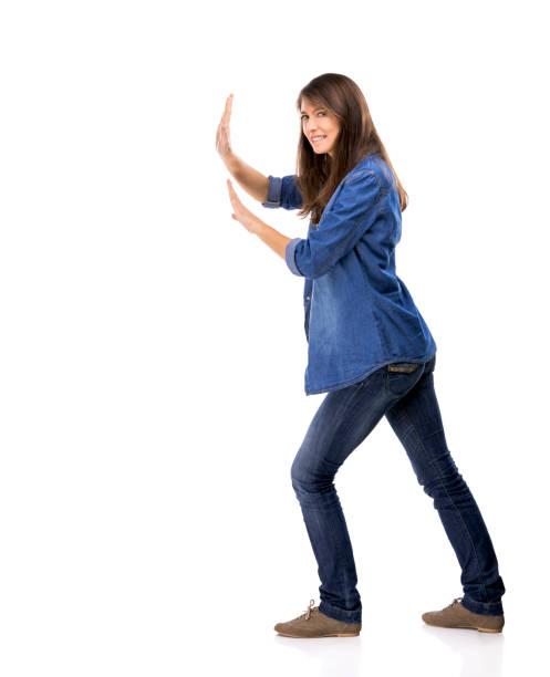 Beautiful woman push something over a white background stock photo