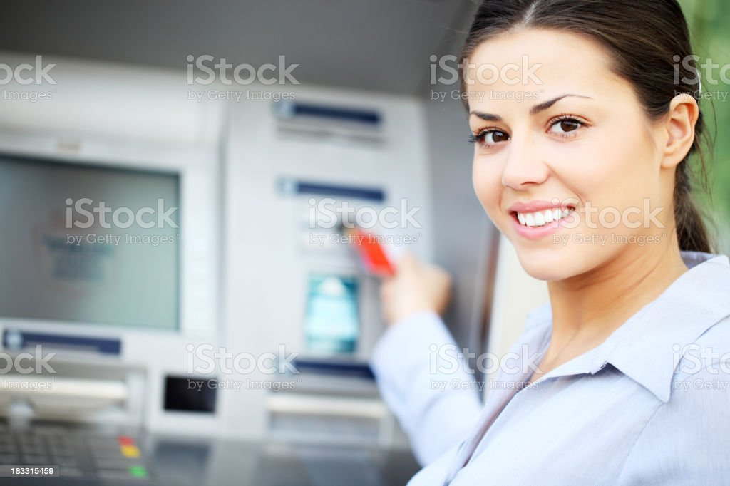 Beautiful woman put her credit card at the ATM. royalty-free stock photo