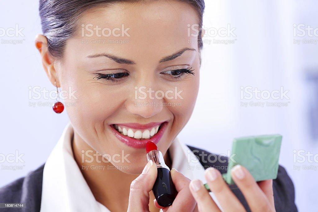 Beautiful woman puts red lipstick on lips. royalty-free stock photo