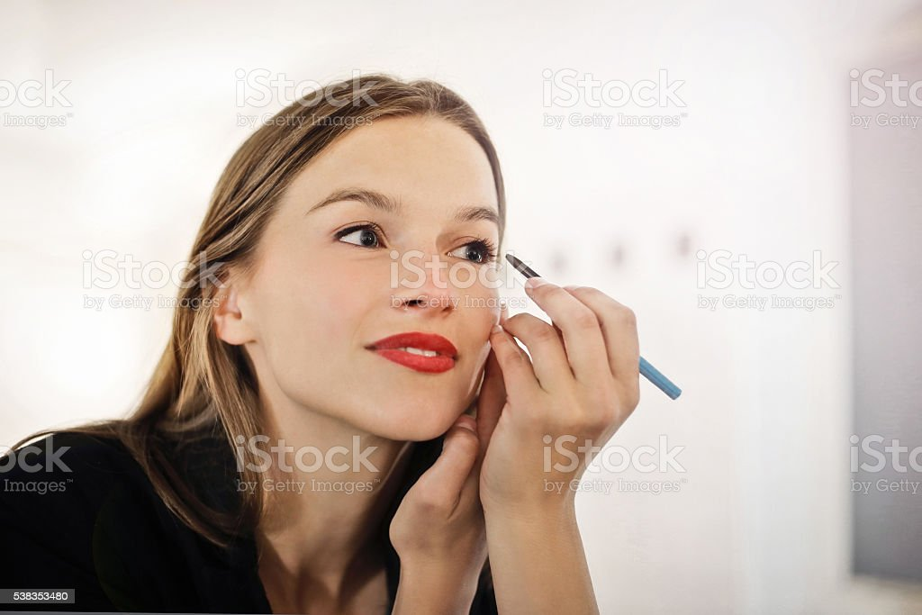 beautiful woman putting make-up on stock photo