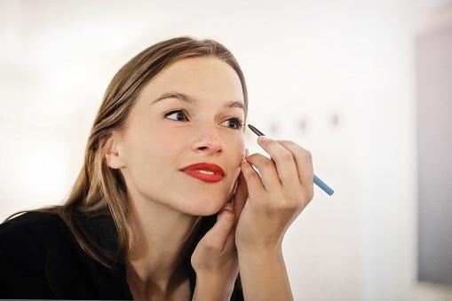 beautiful woman putting make-up on stock photo