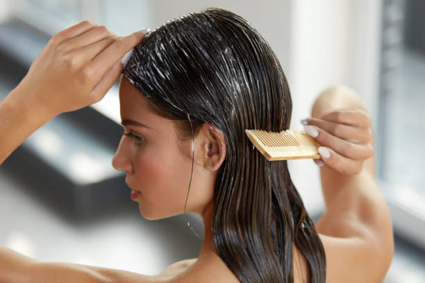 Beautiful Woman Putting Mask On Long Wet Hair. Hairbrushing stock photo
