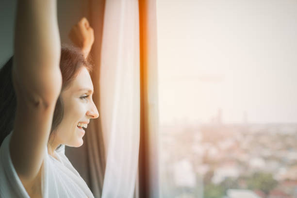 Beautiful woman raising hands and get fresh air in morning with smile face at luxury hotel or condominium, high building. Gorgeous girl looks through window for seeing nice view with city background stock photo