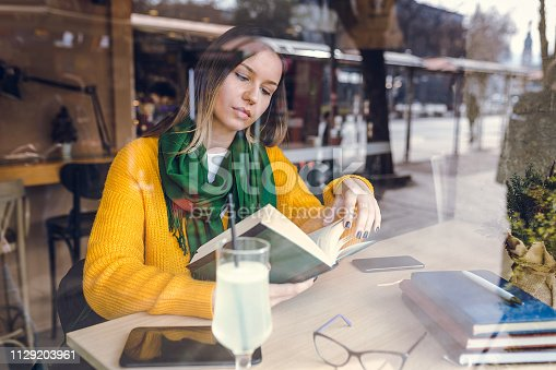1183295518 istock photo Beautiful woman reading a book in a cafe 1129203961
