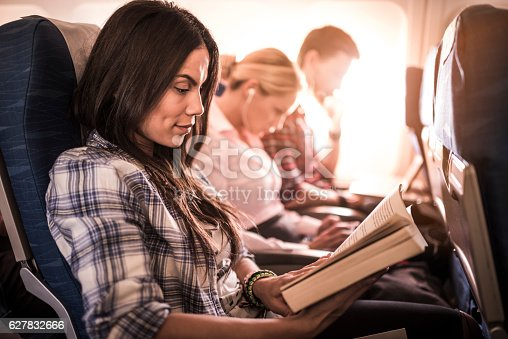 Young woman sitting in an airplane with other passengers and enjoying in a book.