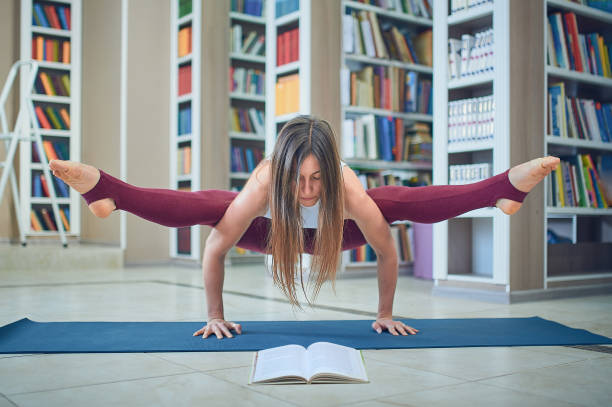 Beautiful woman reading book and practices handstand yoga asana Tittibhasana - firefly pose in the library stock photo