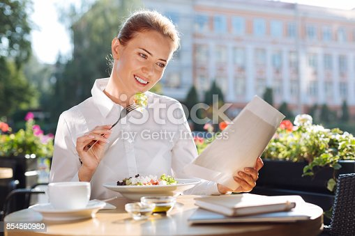 istock Beautiful woman reading documents while eating out 854560980