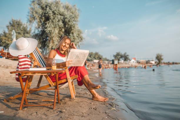 mooie vrouw lezen van de krant op het strand - newspaper beach stockfoto's en -beelden