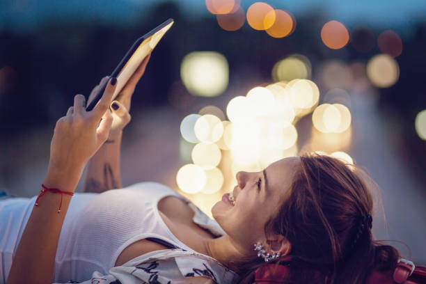 Beautiful woman reading on her tablet outdoors in the city stock photo