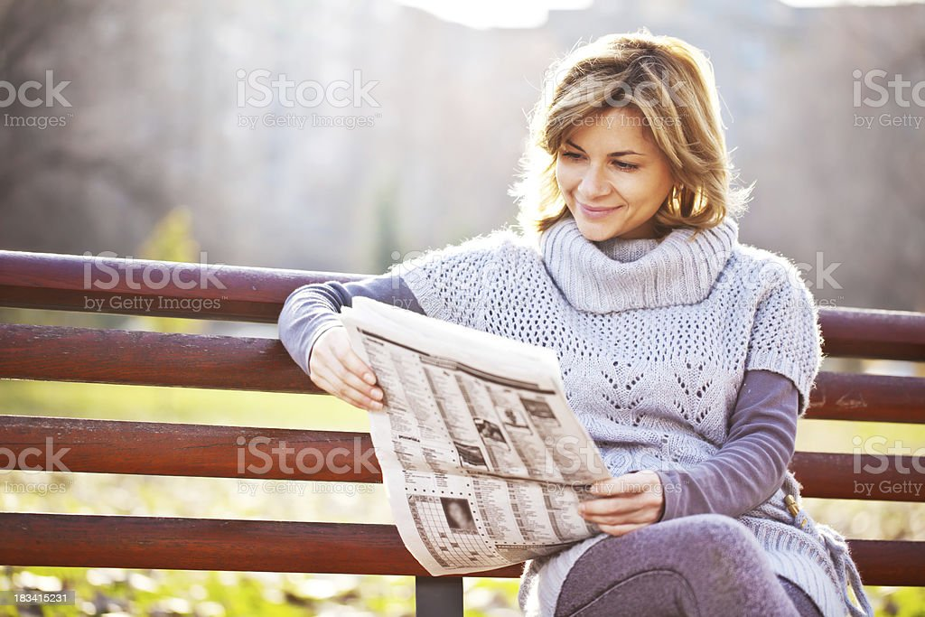Beautiful woman reads a newspaper at the park. stock photo