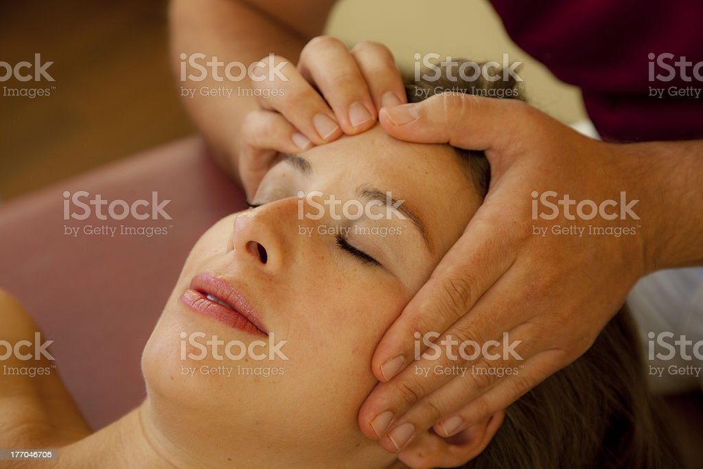 beautiful woman receives a pressure point massage close up stock photo