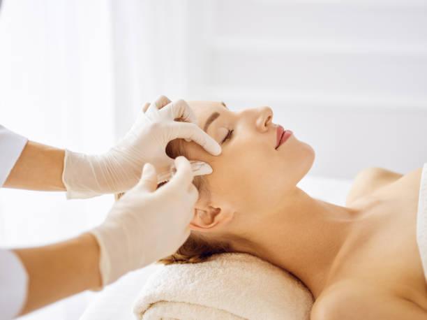 Schöne Frau, die Schönheitsspritzen mit geschlossenen Augen erhält. Kosmetikerin Arzt Hände tun Schönheit Verfahren, um weibliche Gesicht mit Spritze. Kosmetikmedizin und Operationskonzept – Foto
