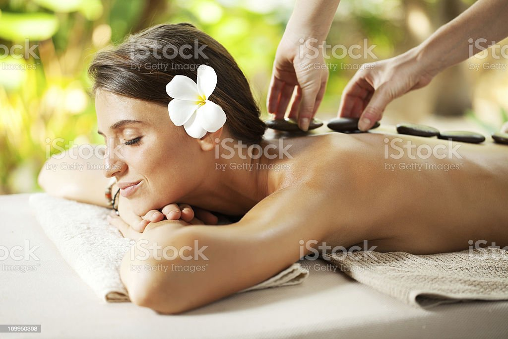 Beautiful woman receiving hot stone therapy. royalty-free stock photo
