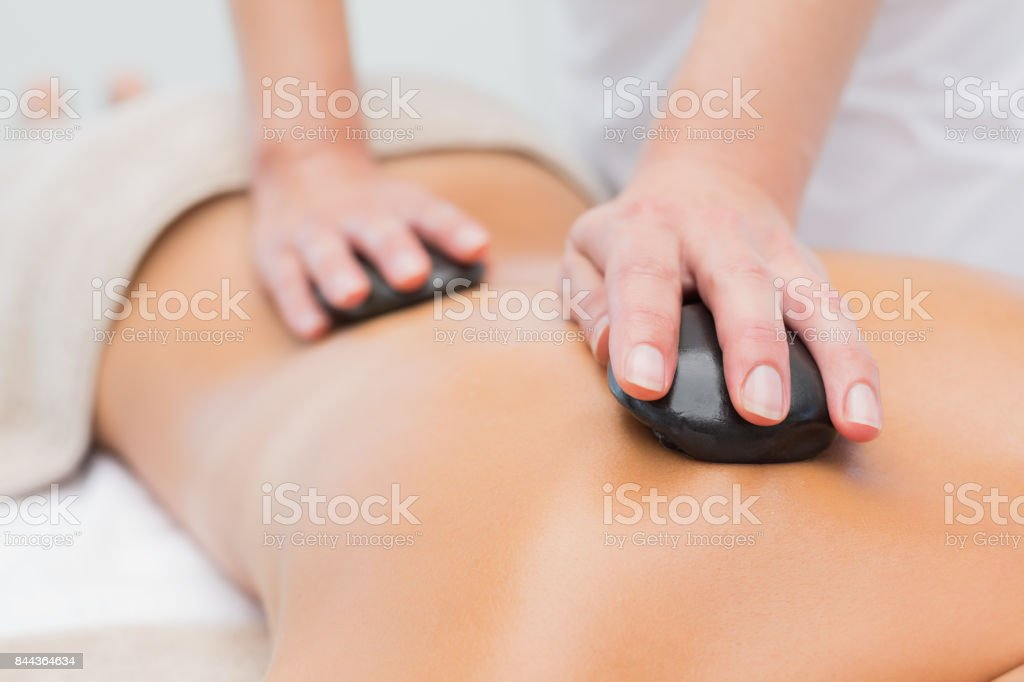 Beautiful woman receiving stone massage at spa center stock photo