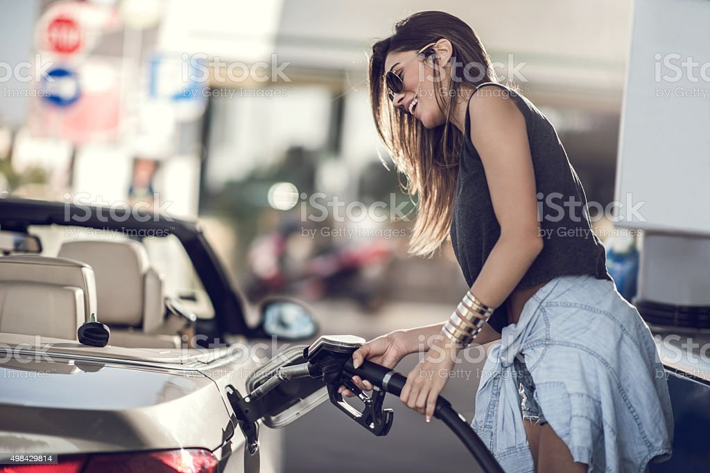 Beautiful woman refueling the gas tank at fuel pump. royalty-free stock photo