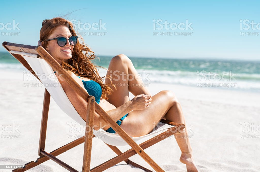 Beautiful woman relaxing at beach Happy young woman relaxing on deck chair at beach while looking at camera. Cheerful mature woman with red hair wearing sunglasses and blue bikini enjoying vacation at beach. Sunbathing and relaxing at sea on a sunny day with copy space. Adult Stock Photo