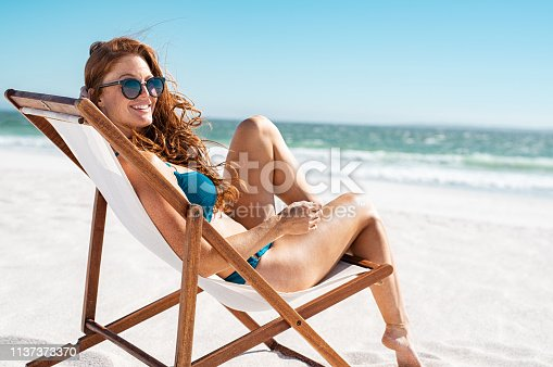 Happy young woman relaxing on deck chair at beach while looking at camera. Cheerful mature woman with red hair wearing sunglasses and blue bikini enjoying vacation at beach. Sunbathing and relaxing at sea on a sunny day with copy space.