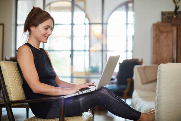 Beautiful woman relaxing at home with laptop. stock photo