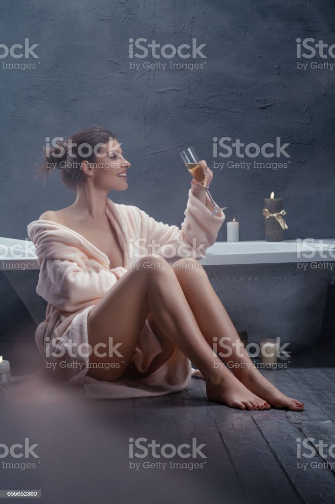 Beautiful woman relaxing in bathrobe holding a glass of champagne stock photo