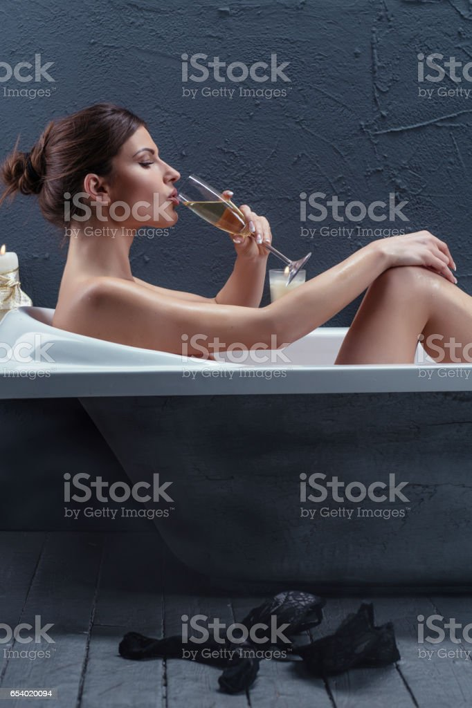 Beautiful woman relaxing in bathtub drinking champagne stock photo