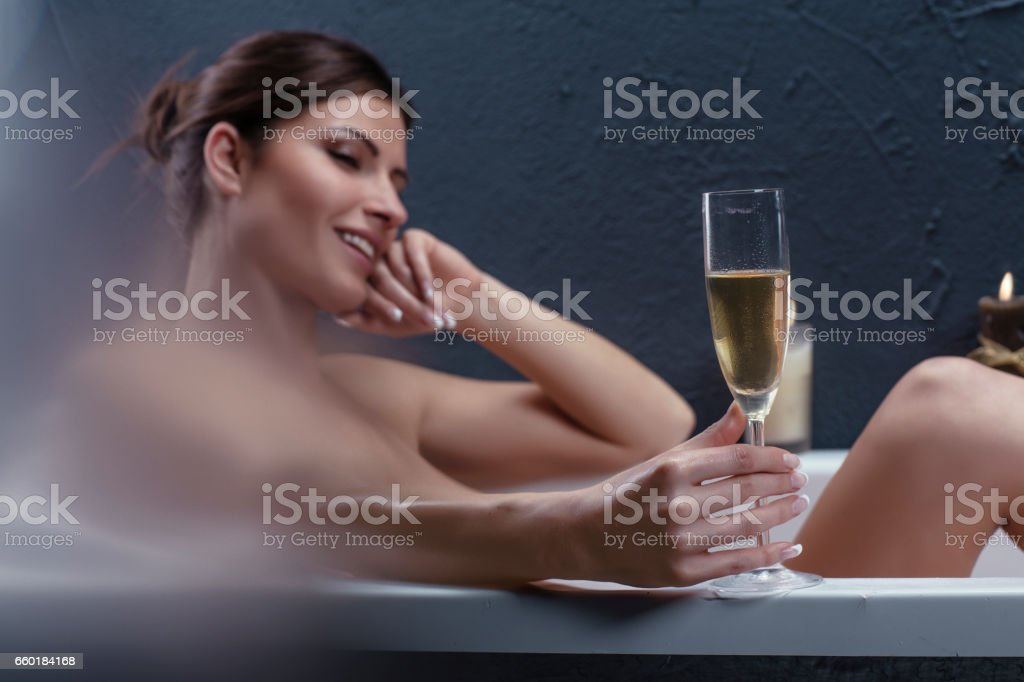 Beautiful woman relaxing in bathtub holding a glass of champagne stock photo