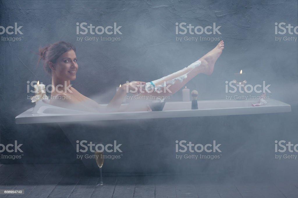 Beautiful woman relaxing in bathtub shaving legs stock photo