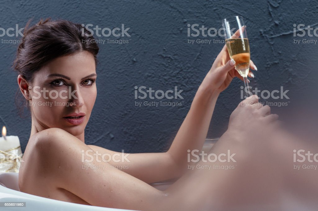 Beautiful woman relaxing in bathtub with lighted candles. 29 years woman taking a bath and drinking champagne. Steamy.New Age Beauty & Wellness stock photo