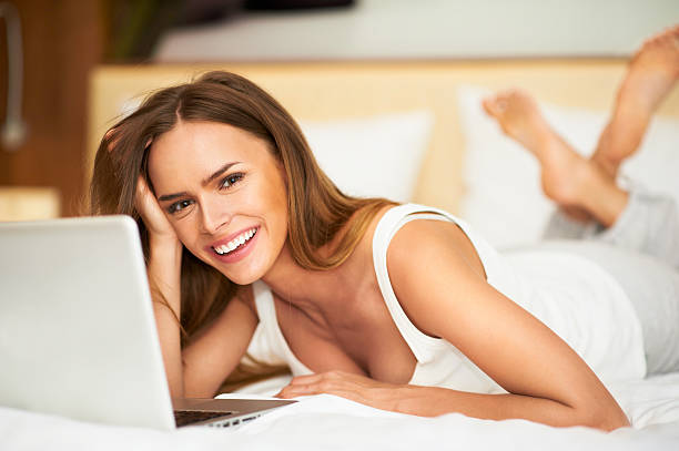 Beautiful woman relaxing in bed in white undershirt using laptop stock photo