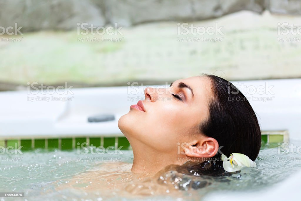 Beautiful woman relaxing in jacuzzi at health spa royalty-free stock photo
