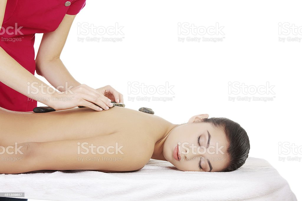 Beautiful woman relaxing in spa. Stone massage. royalty-free stock photo