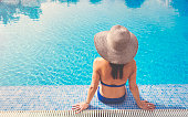 Beautiful Woman relaxing in blue swimming pool with  blue Bikini and sun hat