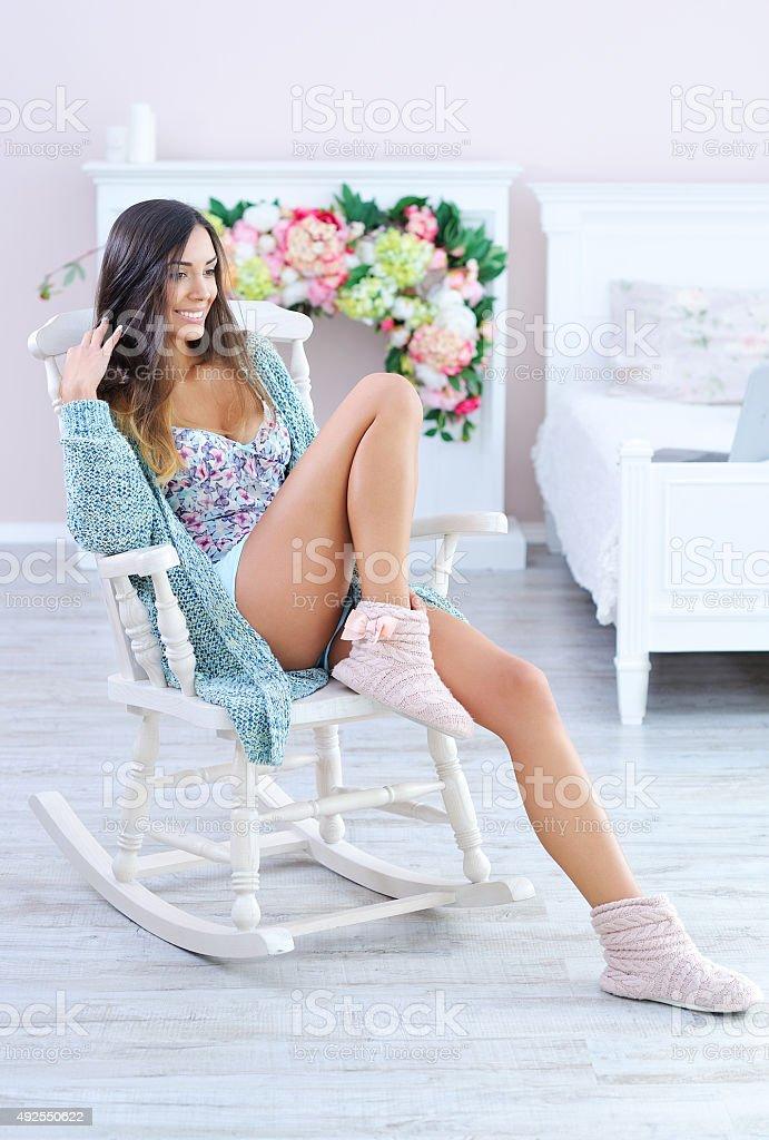 Mulher bonita e relaxante na cadeira de balanço de branco - foto de acervo