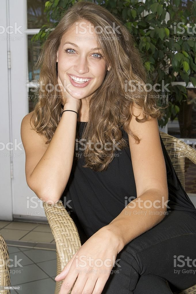 Beautiful Woman Relaxing on a Patio Chair royalty-free stock photo