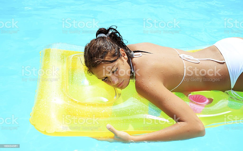 Beautiful woman relaxing on inflatable mattress in pool. royalty-free stock photo