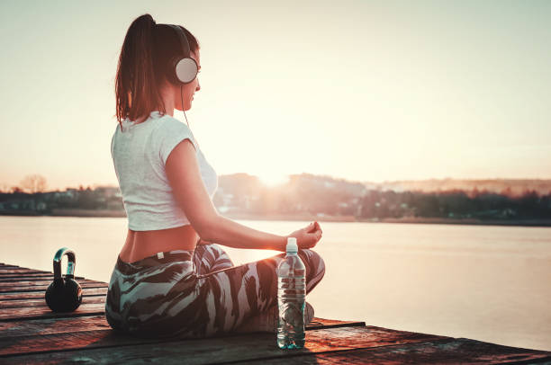 Beautiful woman relaxing outdoors after running workout. Yoga position towards sun stock photo