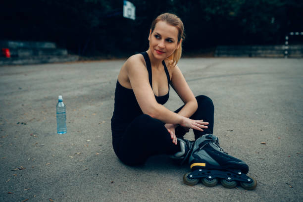 Beautiful woman resting after an exercise with inline skates stock photo